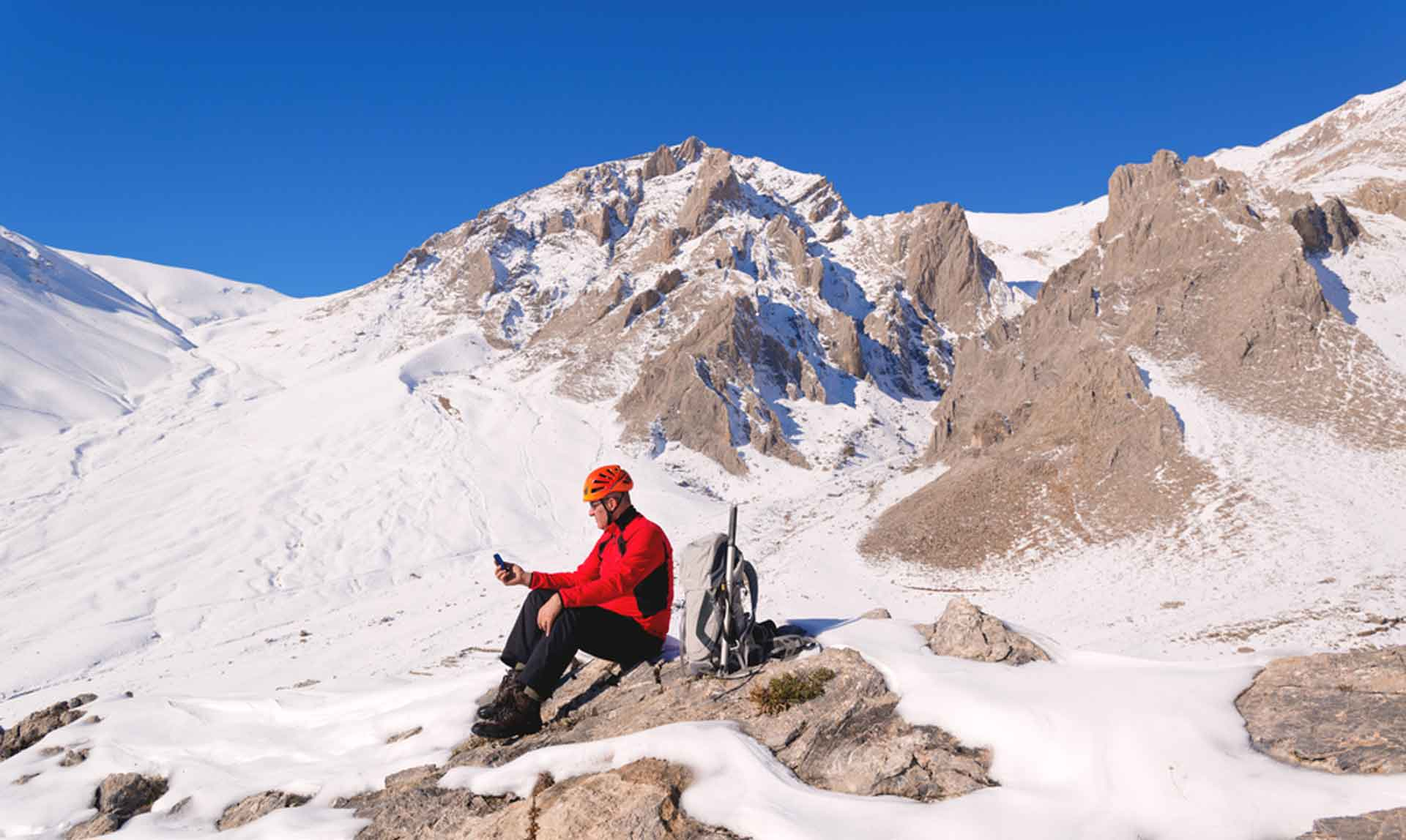 man sat on a snowy mountain placing an order using his phone